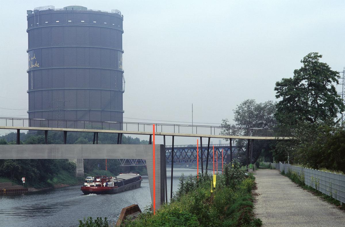 Foto der Marinabrücke (Tausendfüssler) in Oberhausen im südlichen Teil der Brücke, der den Rhein-Herne-Kanal überspannt. Die Brücke ist als gewellter Betonteppich ausgebildet, der auf Stützen auflagert. Im Bereich der Überspannung der Kanäle nehmen große Betonrahmen die Kräfte der Stützen auf.