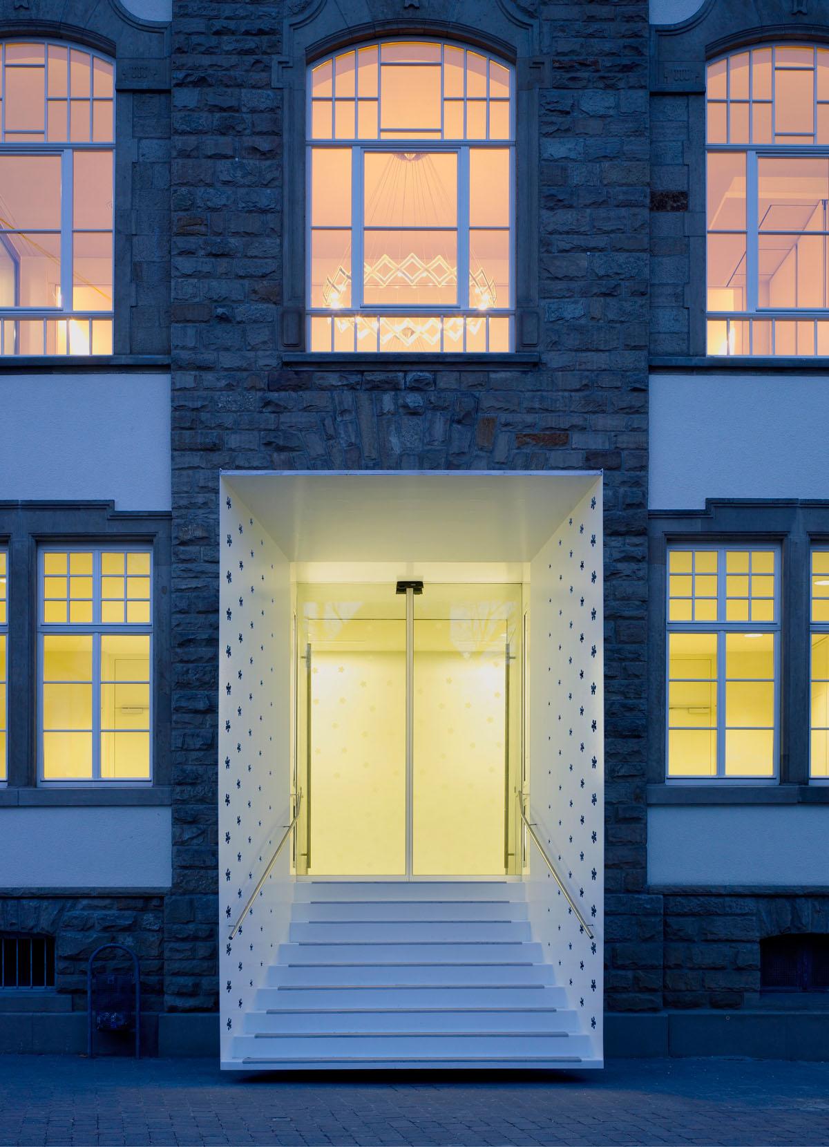 Foto des Haupteingangs des neuen evangelischen Gemeindezentrums Lutherhaus der Kirche in Hockenheim. Der Haupteingang schiebt sich in die Straßenflucht in Form eines eckigen Trichter. Er ist in weiß gehalten und mit einer Perforierung von Rosen, dem Wappen Luthers, überzogen.