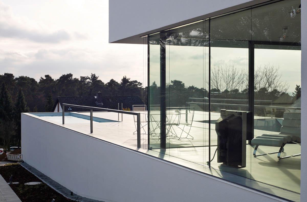 Foto des Einfamilienhauses M in Darmstadt. Blick durch den verglasten Wohnraum und über die Sonnenterrasse mit Swimmingpool in Richtung Rheinebene.