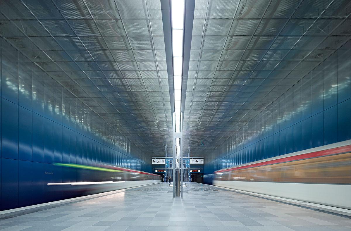 Foto der U-Bahnstation Überseequartier in der HafenCity Hamburg. Die Station ist die Inszenierung einer Unterwasserwelt. Durch einen Farbverlauf der Wände nach oben von dunkel- zu hellblau und dem Wechsel zu spiegelnder Materialität entsteht der Eindruck man befinde sich in der Tiefe des Meeres. Die bewegte Decke ist hell und reflektiert Licht, sie ist scheinbar die Wasseroberfläche, die man von unten beobachten kann.