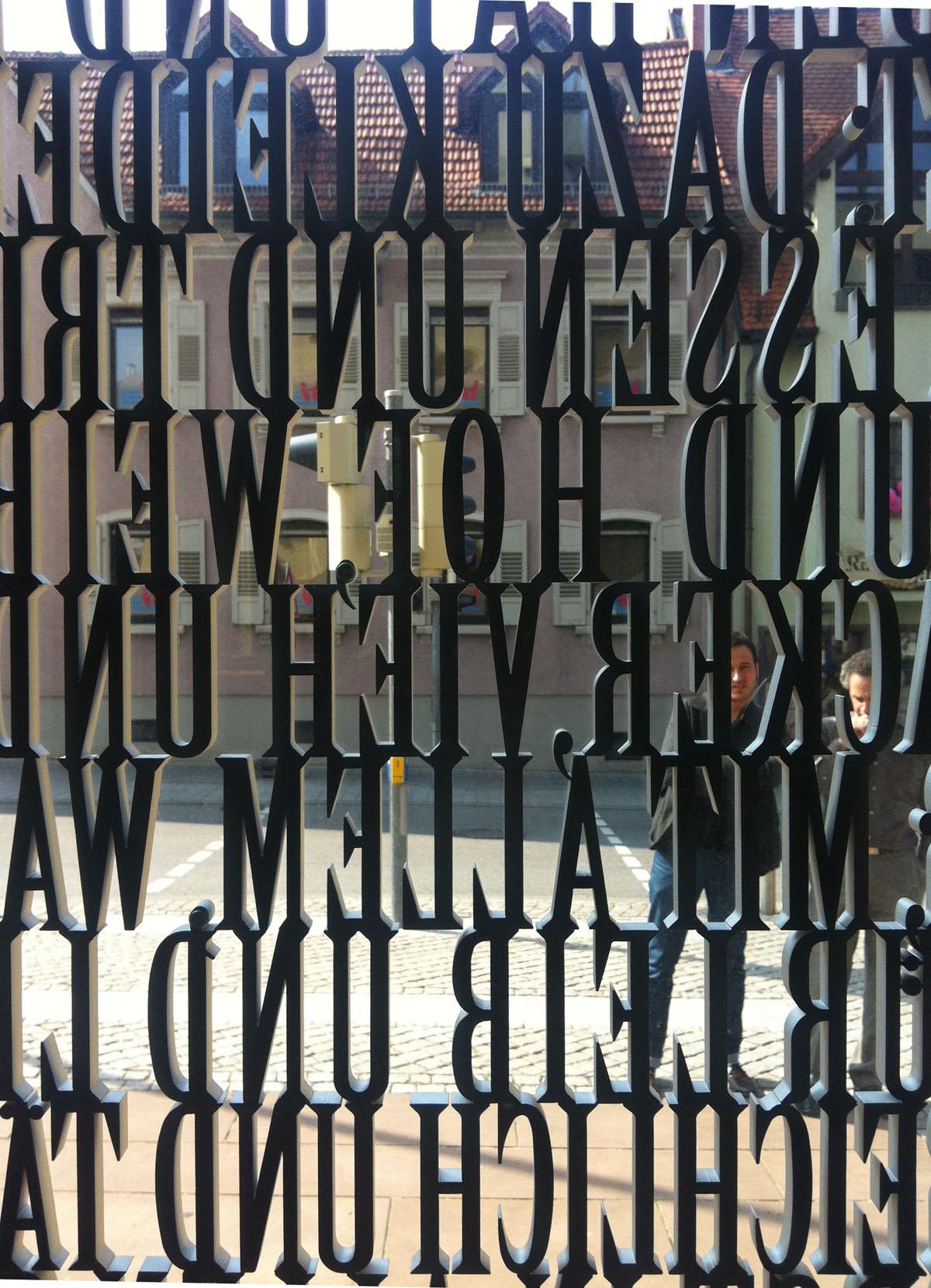 Blick durch das Kirchenportal der evangelischen Kirche in Walldorf. Das Portal ist aus Glasscheiben mit einem Alumniumgitter aus Textpassagen gestaltet. Zwischen den Buchstaben erhält man einerseits den Blick nach draußen, andererseits gelangt Tageslicht in den Kircheninnenraum.