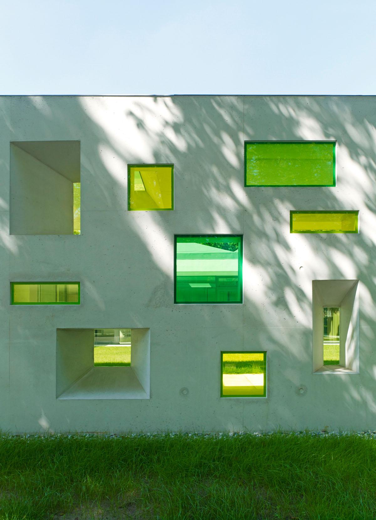 Foto der Südfassade des evangelischen Gemeindezentrums Zeilsheim von außen. Moderne Interpretationen von Kirchenfenstern in scheinbar chaotischer Anordnung in die Mauer eingefügt. Rechteckige Öffnungen, die als Trichter ausgebildet sind, mit Glasscheiben in unterschiedlichen Grüntönen.