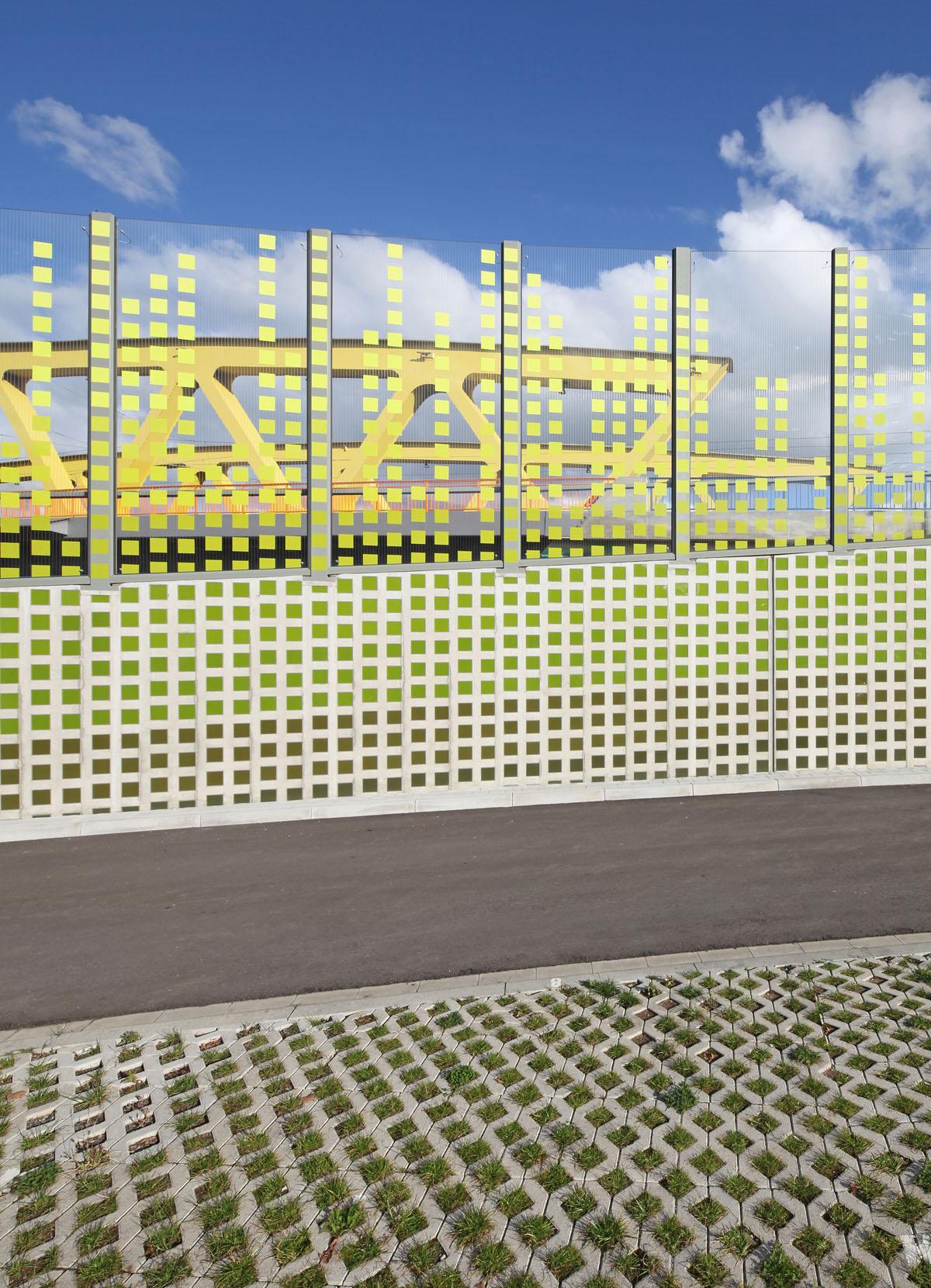 Bild der Lärmschutzwand an der Südtangente in Mannheim. Foto der Wand über die ganze Höhe. Teilung in Stützwand aus Stahlbeton unten und darauf Glasscheiben. Raster aus grünen Pixeln löst sich im Glasbereich unregelmäßig auf. Dahinter erkennt man das Rampenbauwerk.