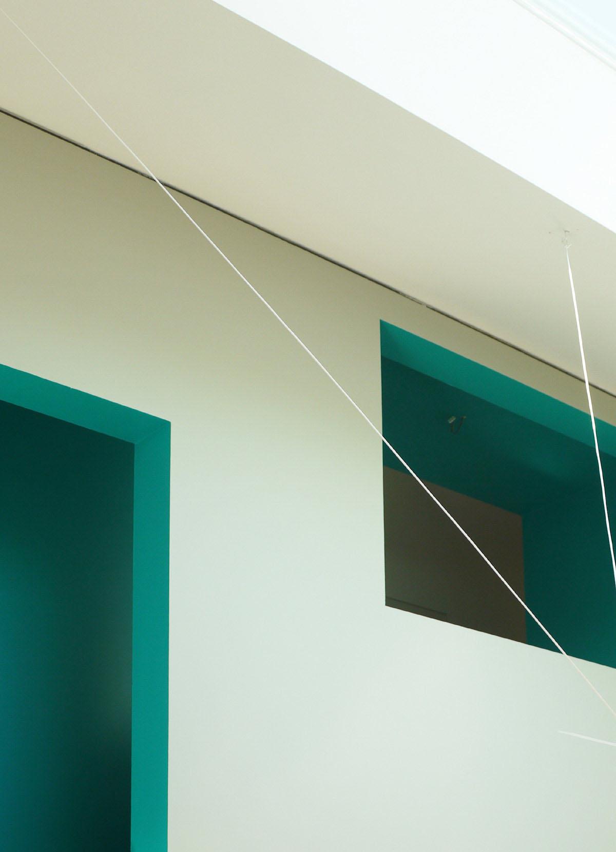 Foto des Mehrfamilienhauses im Hinterhof der Niederstraße 25 in Altbessungen, Darmstadt. Blick in den Innenraum des Dachgeschosses. Detailfoto der Einschnitte im Treppenkern. Farbige Laibungen kontrastieren die Öffnungen zur weissen Wand.
