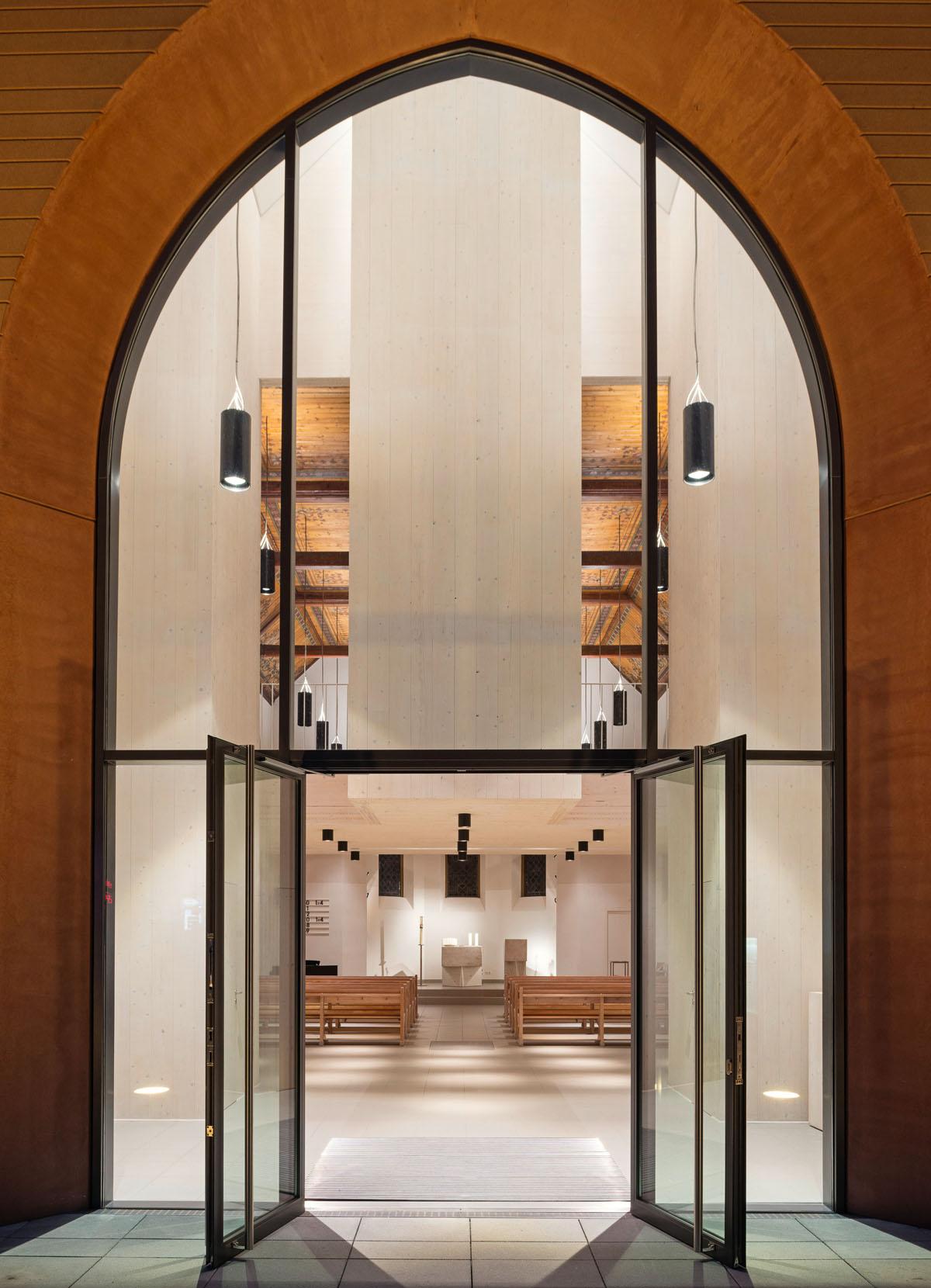 Blick von außen nach in den Kirchenraum der Evangelischen Kirche in Altenbach. Das Gläserne Eingangsportal bietet einen guten Einblick in den Innenraum.