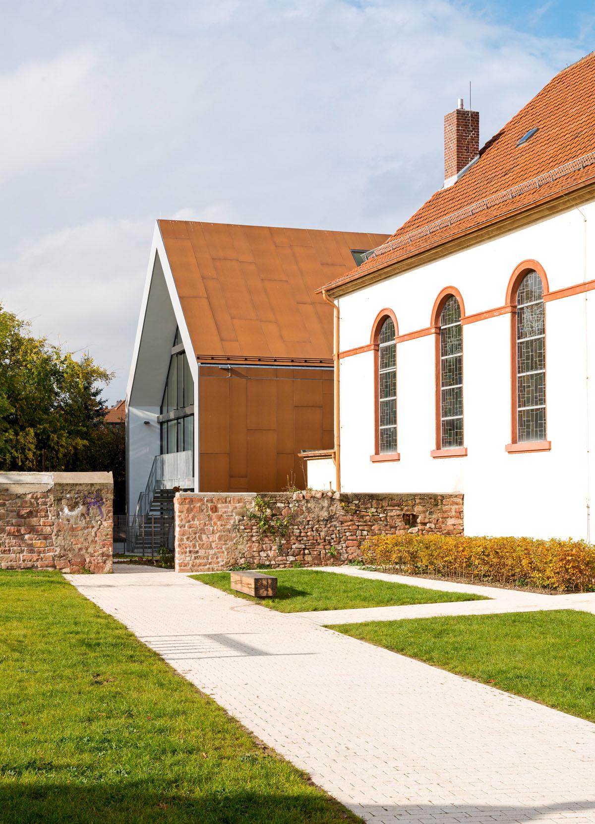 Bild des Gemeindehauses der Unionsgemeinde in Mannheim-Käfertal. Blick vom Park über die Umfassungsmauer auf das Gemeindehaus, das hinter der Kirche hervorschaut.