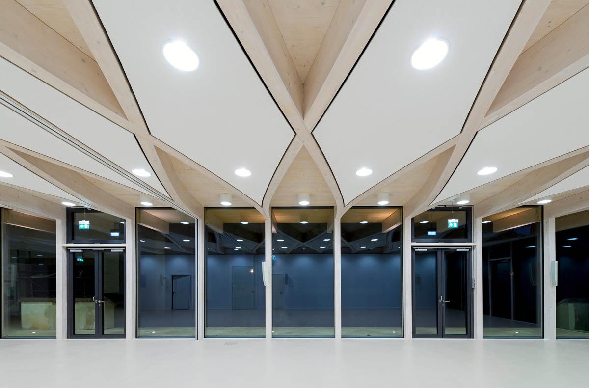 Bild des Gemeindehauses der Emmausgemeinde in Heidelberg-Pfaffengrund. Blick auf die Innenseite der Glasfassade des Gemeindesaals. Heller Saal mit dynamisch geschwungener Tragstruktur der Decke.