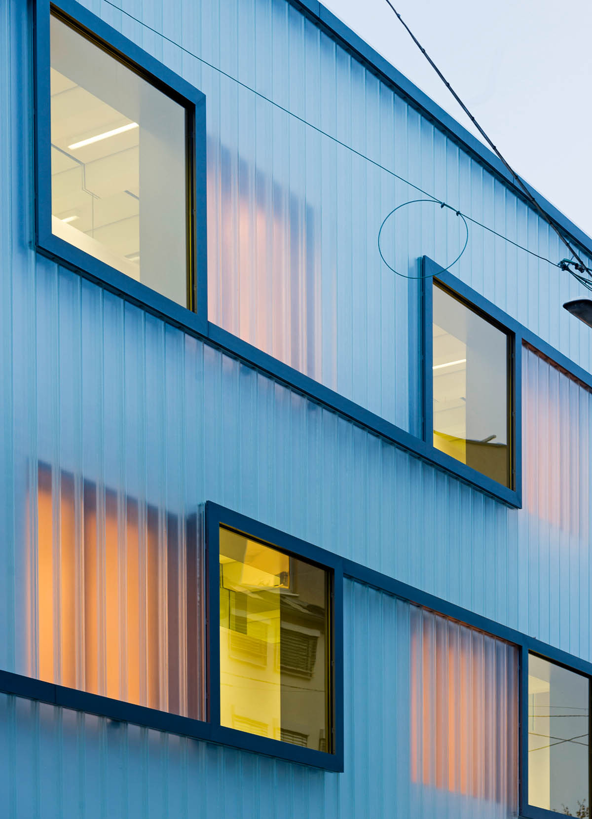 Nahaufnahme der Fassade des Fichtegymnasiums in Karlsruhe. Farbig verspiegelte Fenster, die durch ein dunkles Band verbunden sind. Hinter der plastischen Glasfassade erahnt man weitere Fenster.