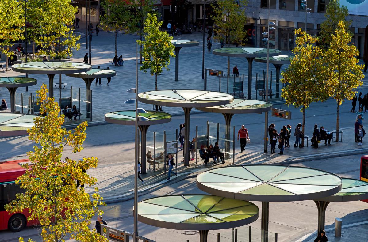 Blick auf den ZOB Hanau. Die neuen Überdachungen der Haltestellen gliedern sich in den Baumbestand ein und bieten Wartenden Schutz.