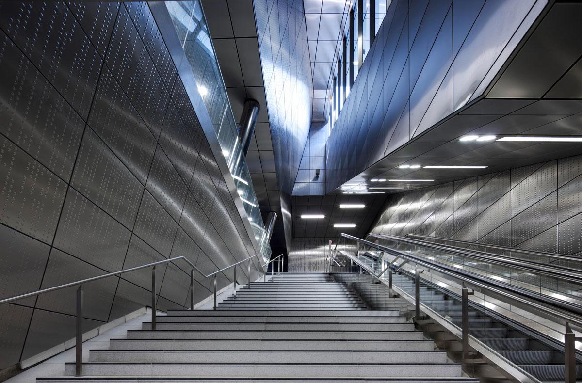 Bild der U-Bahn Station Benrather Strasse der Wehrhahnlinie in Düsseldorf. Blick vom Fuß der Treppe hinauf. Glänzende Edelstahlverkleidung der Wände. Tageslicht fällt in die unterirdischen Räume.