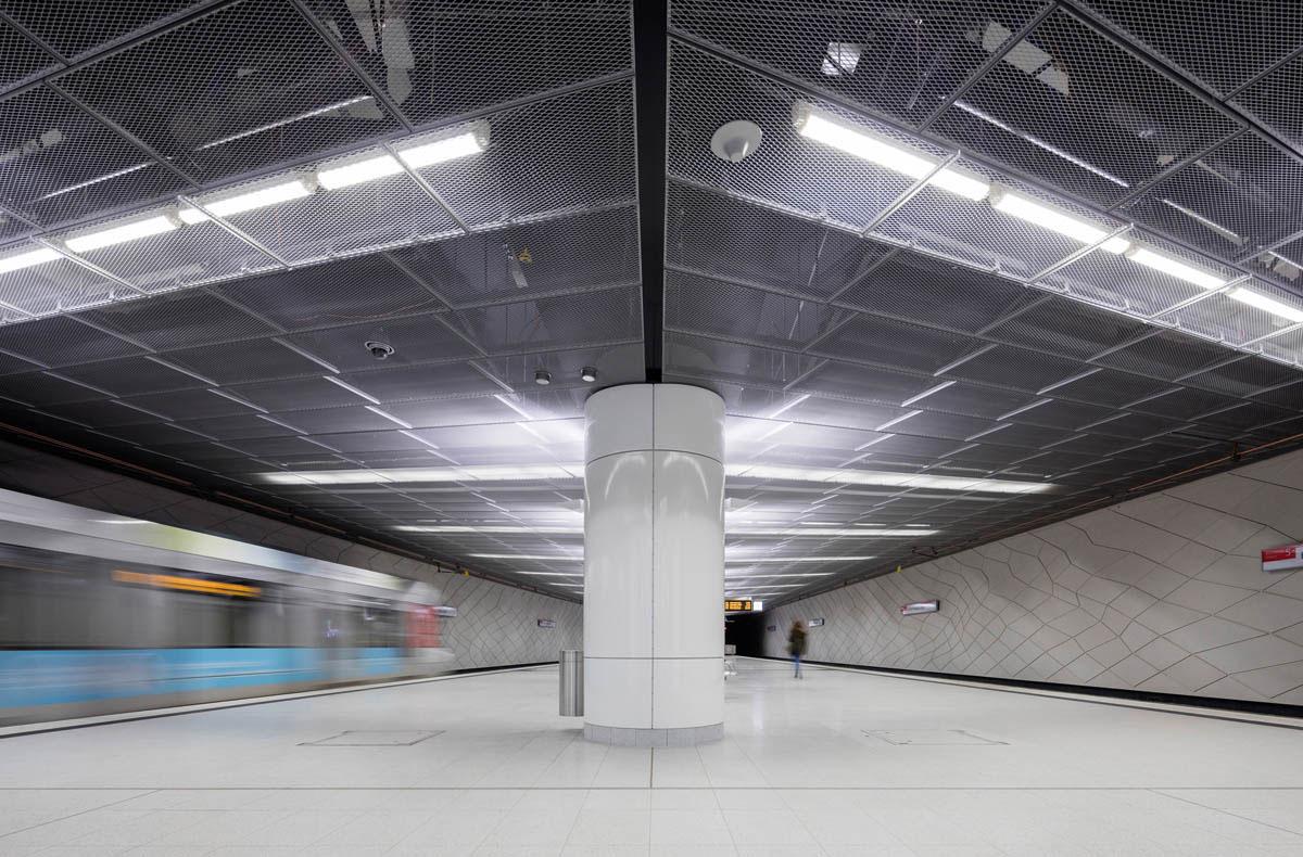 Bild des Mittelbahnsteigs der U-Bahnstation Heinrich-Heine-Allee der Wehrhahnlinie in Düsseldorf. Blick auf den Bahnsteig und die Gleise auf beiden Seiten.