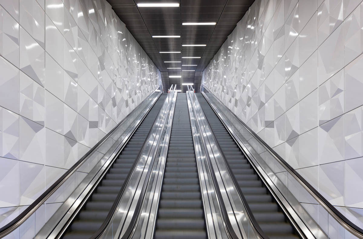 Bild der U-Bahnstation Heinrich-Heine-Allee der Wehrhahnlinie in Düsseldorf. Blick die Rolltreppen hinauf zur Verteilerebene. Dreidimensional geformte Wandelemente belegen die Wände. Dieser Zugang hat den Namen Auditorium.