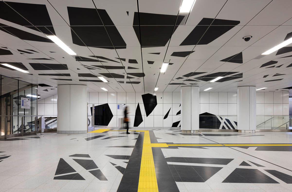 Bild der U-Bahnstation Pempelforter Straße der Wehrhahnlinie in Düsseldorf. Blick auf die Verteilerebene. Auf Boden, Wänden und Decke entfaltet sich die Kunst der Station, ein unregelmäßiges Netz aus weissen Linien auf schwarzem Grund.