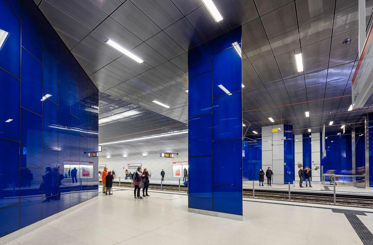 Bild der Fahrebene der U-Bahnstation Schadowstraße der Wehrhahnlinie in Düsseldorf. Wartende Menschen stehen auf den Bahngleisen. Die Wände sind mit farbigem Glas verkleidet.