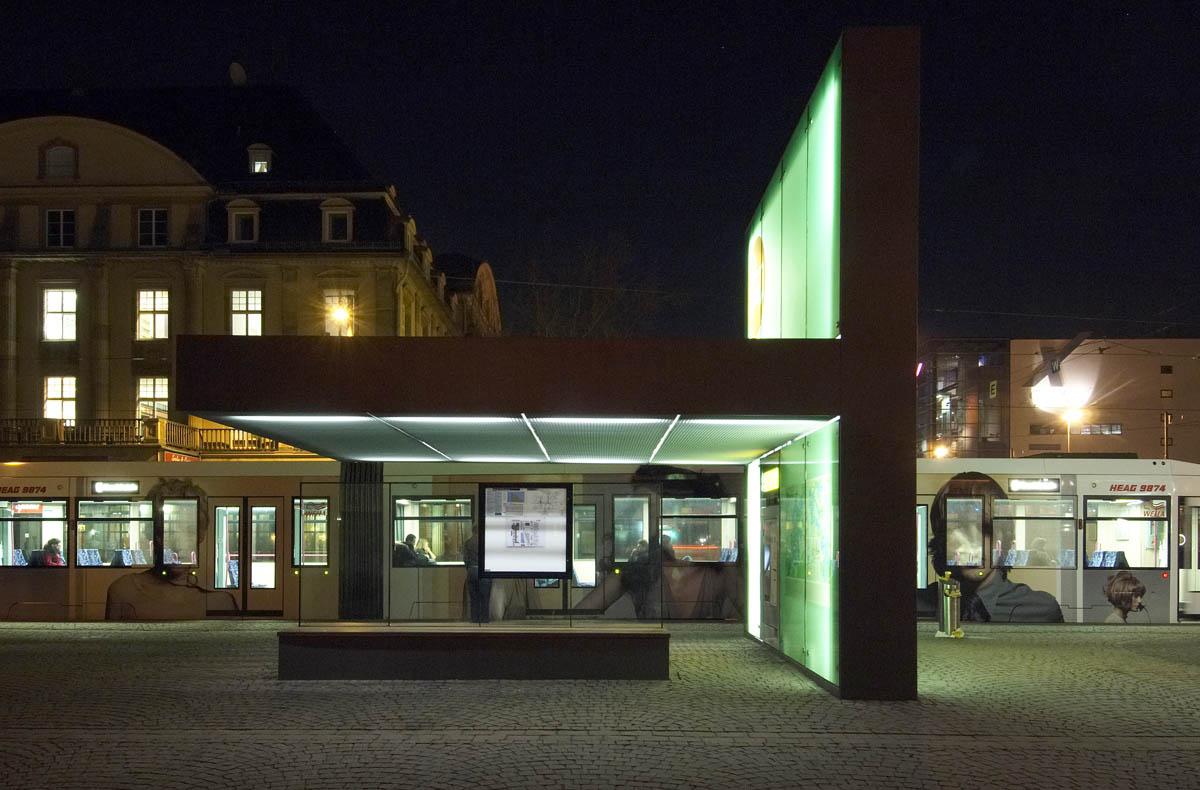 Foto einer der neuen Haltestellen am Hauptbahnhof in Darmstadt. Ein überdimensionaler, gefalteter Leuchtkörper entsteht aus dem Boden. Unter seiner auskragenden Fläche finden die Fahrgäste Schutz vor der Witterung. Durch die Konstruktion der Auskragung, kann diese stützenfrei bleiben.